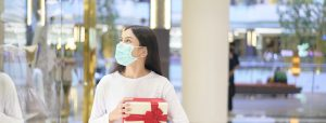 Woman Wearing Protective Mask Holding A Gift Bo In Shopping Mall, Shopping Under Covid Pandemic, Thanksgiving And Christmas Concept.